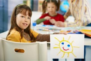 little girl showing her artwork